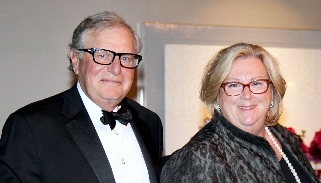 man in tuxedo, left, smiling and wearing glasses, and his wife, right, blond