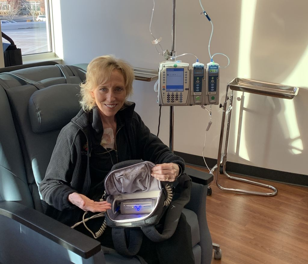A thin blonde woman in a black jacket sits in a recliner with a machine in the backpack on her lap in a medical clinic