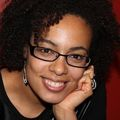 close-in headshot of Raina Croff, Ph.D., a smiling Black woman in glasses resting her chin on her left hand.