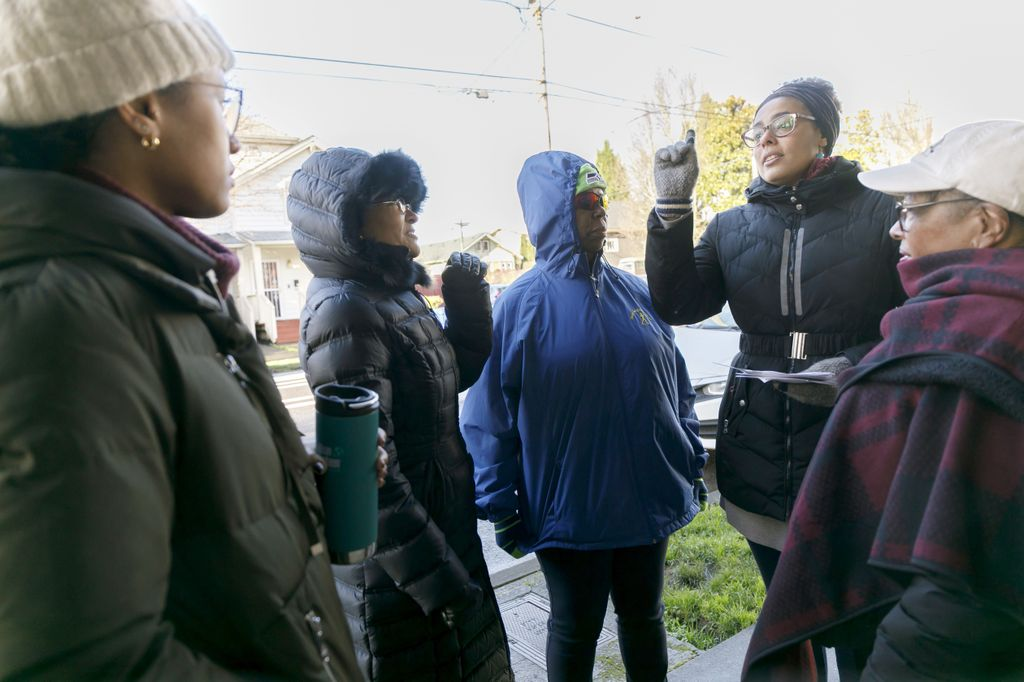 Raina Croff directs participants in her Sharing History through Active Reminiscence and Photo-Imagery (SHARP) study during a January 14, 2020 walk along North Williams Avenue with guest Camara Jones; the photo includes 5 Black women standing together on a sidewalk in a residential neighborhood.