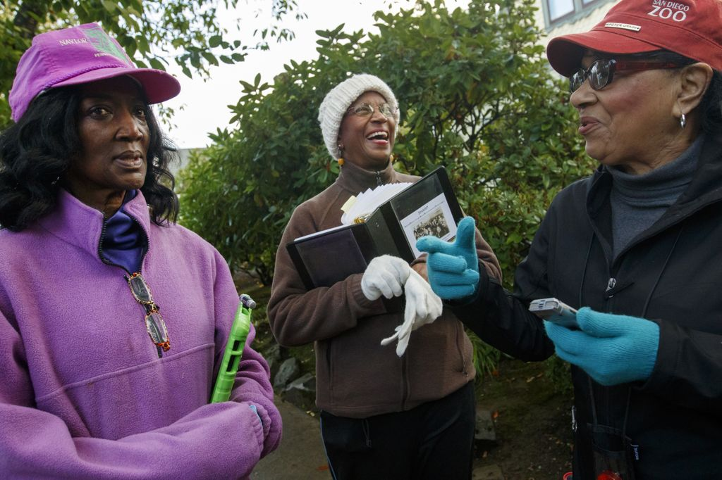 Three smiling Black women in glasses, gloves and hats stand outside in front of a bush