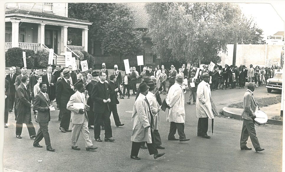 Black and white photo of a 1963 NAACP parade, showing a group of about 50 men, mostly Black and wearing suits or trenchcoats, following a drummer around a residential street corner.