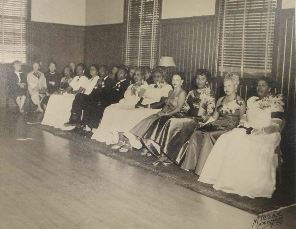 Black and white photo of a Billy Webb Elks Lodge dance, showing a row of seated men and women in formalwear at the edge of a wooden dance floor.