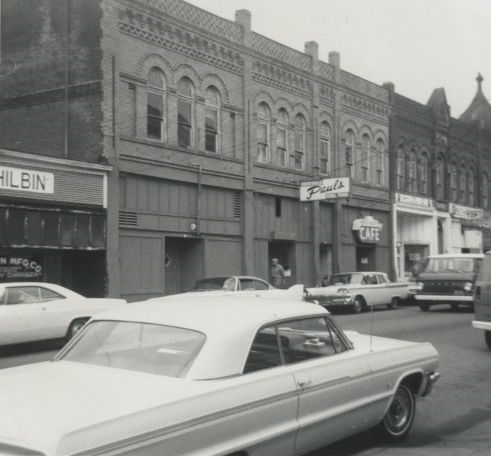 Black and white exterior shot of the entrance to Paul's Paradise Night Club in Portland, OR; a white car is in the foreground.