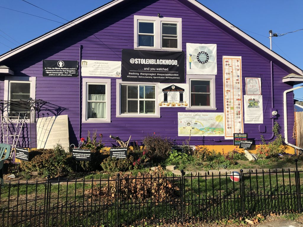 BEAM (Black Educational Achievement Movement)'s homebase in a purple residential home in Portland, OR; there are multiple posters and signs affixed to the outside of the building with messages about community values and stolen blackhood