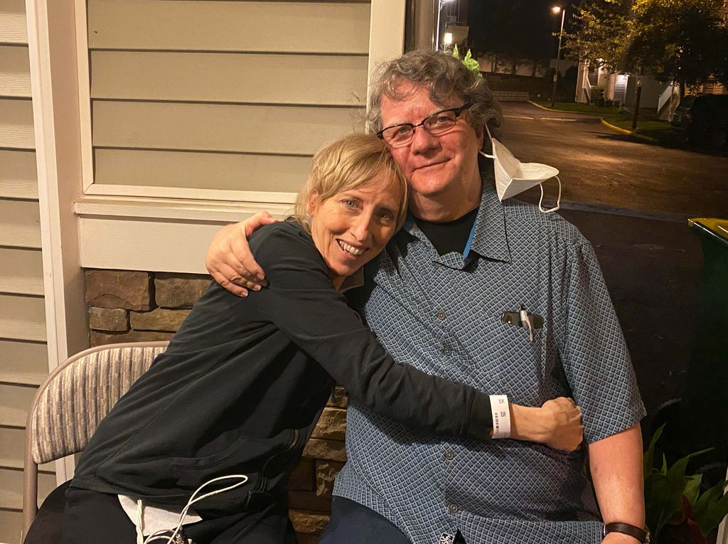 A thin blonde woman has her arms around a grey-haired, smiling man as they sit side by side