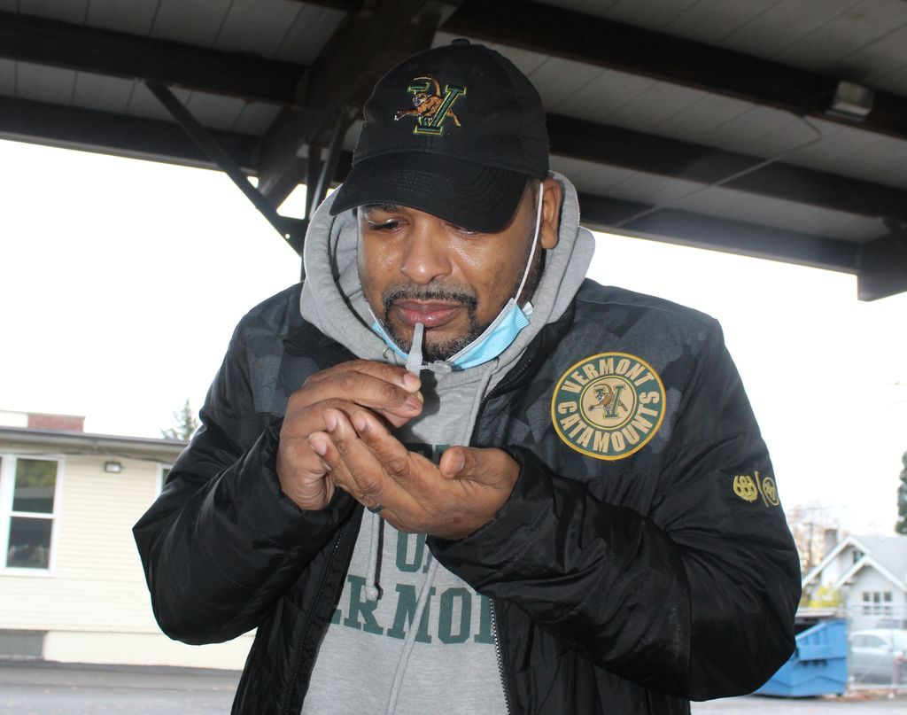 Anthony Deloney, a Black male in a baseball cap, holds in his mouth a vial used for saliva testing for COVID-19