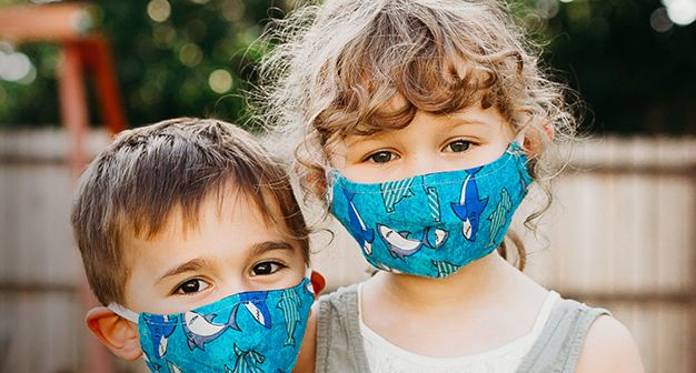 Two young children, a brown-haired boy and blonde girl, stand next to each other while wearing protective masks.
