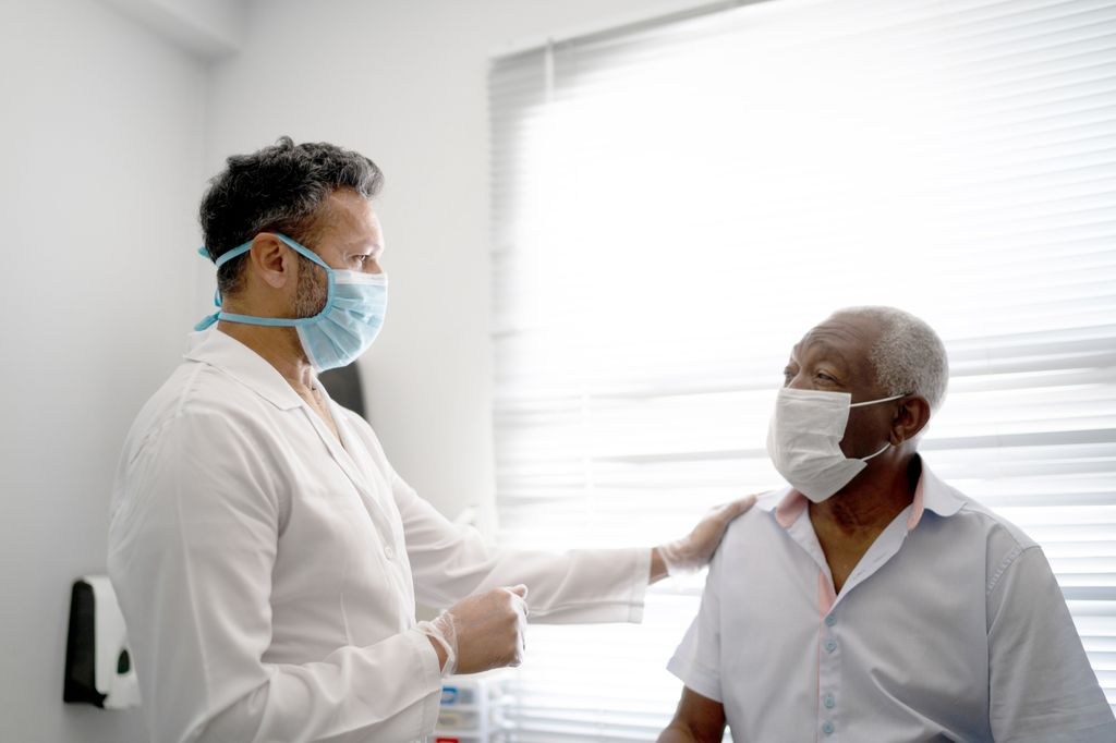 A masked, standing male health care professional in a white lab coat puts his hand on the shoulder of a seated Black male patient