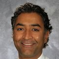 Close-in headshot of Devan Kansagara, a smiling man in a button-down shirt