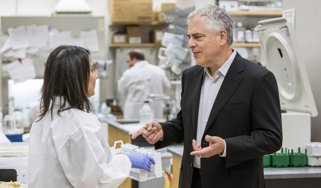 Louis Picker, a white-haired caucasian male, speaks with a female in a white lab coat indoors at the Vaccine and Gene Therapy Institute at Oregon Health & Science University