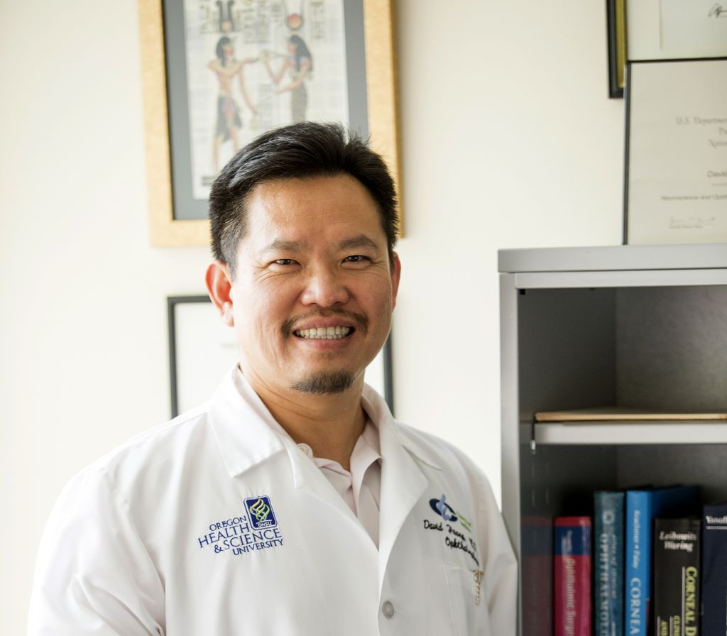 David Huang M.D. Ph.D., an Asian male, stands smiling in front of a bookcase