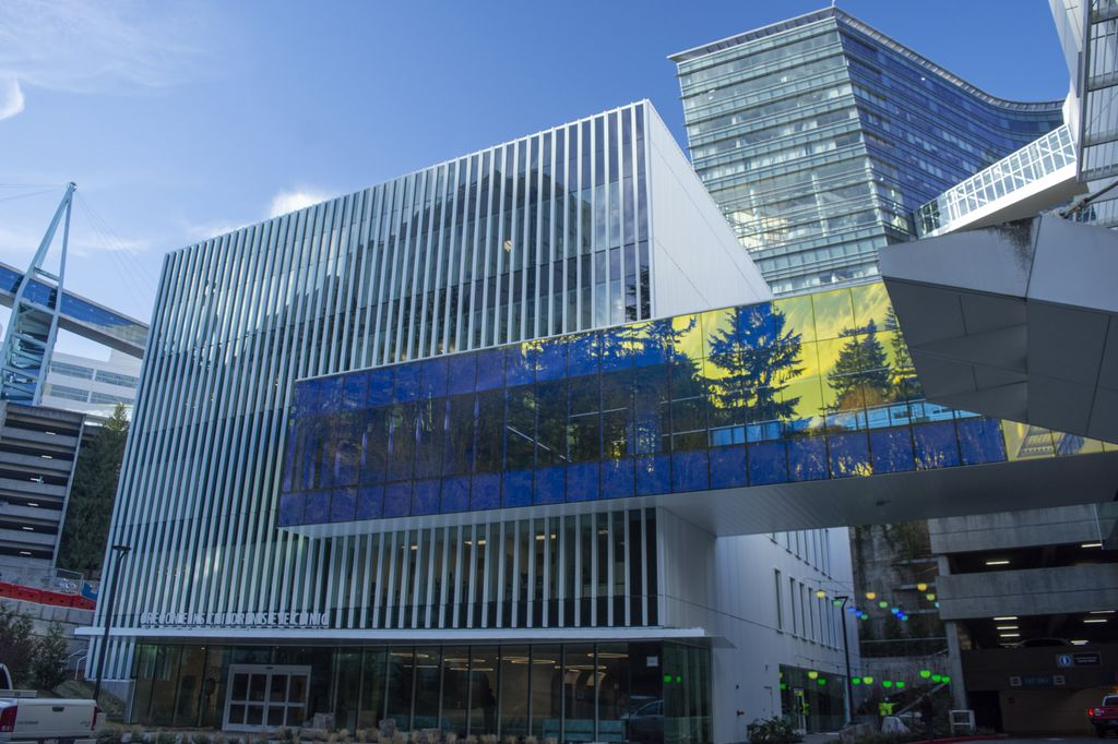 The 60,000 square-foot Elks Children's Eye Clinic building at Oregon Health & Science University's Casey Eye Institute, featureing a striking skybridge between two buildings that is adorned with color-changing glass; in the photo, the glass appears yellow with trees and clouds reflected in blue.