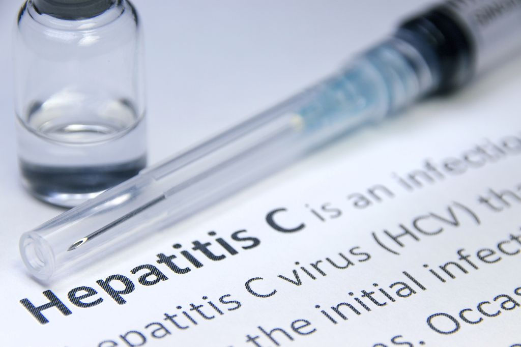 "paperwork with words, ""Hepatitis C"" on it, a capped syringe and vial of clear liquid sitting close by"