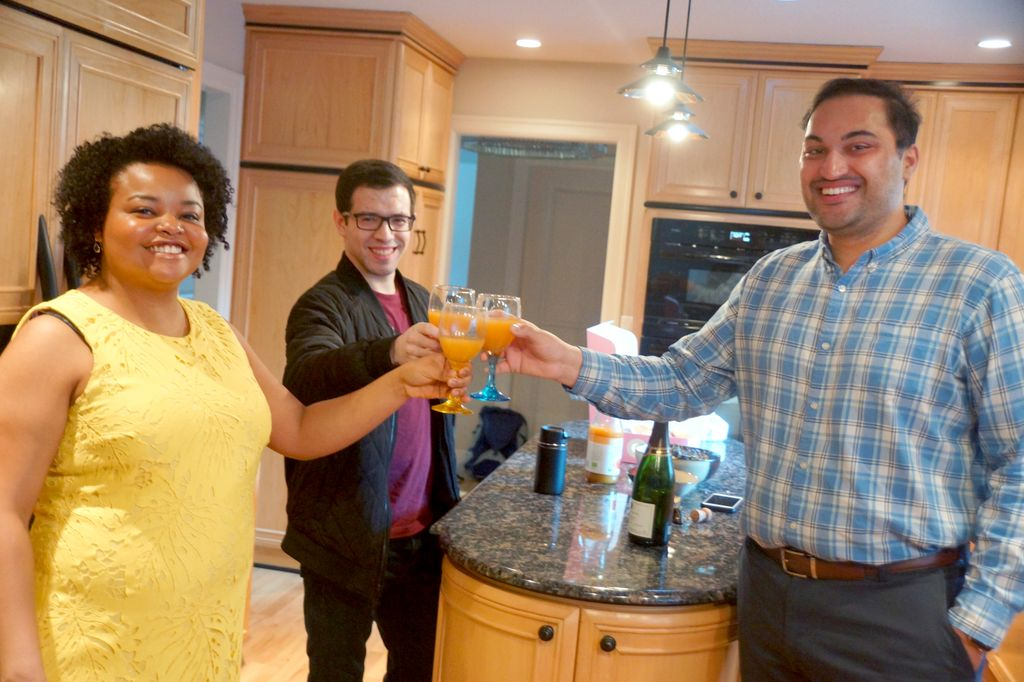 a trio of students stand facing the camera, mimosas in hand and glasses touching in the middle, raised in a toast