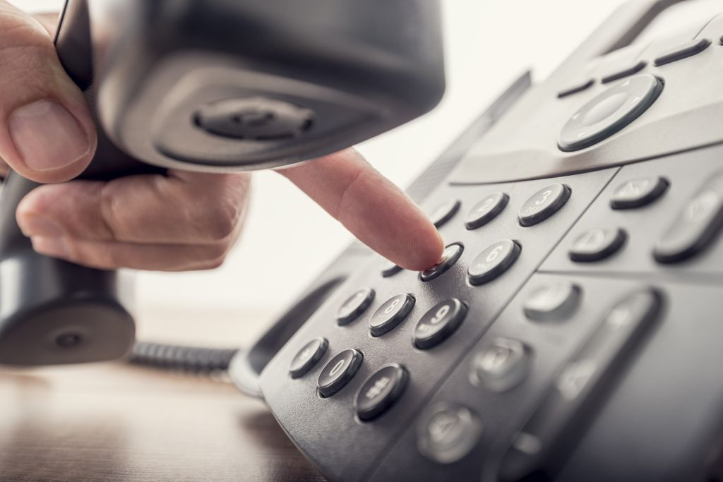close up shot of a hand holding a landline receiver and using one finger to push dial buttons