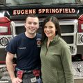 EMt and young woman standing in front of fire truck