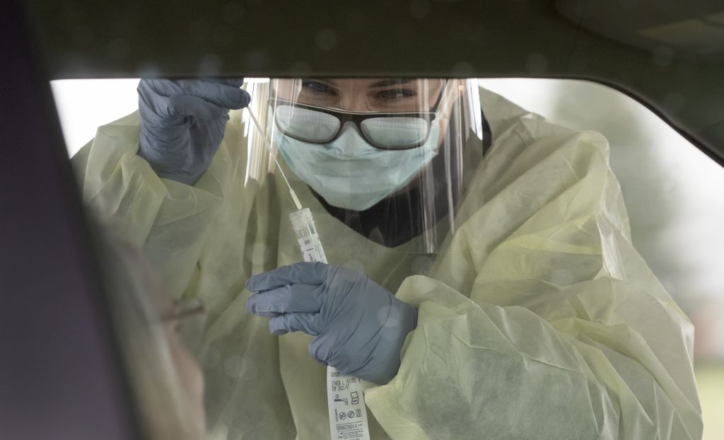 a masked, gloved and gowned female health care worker leans down toward a car window with a cotton swab
