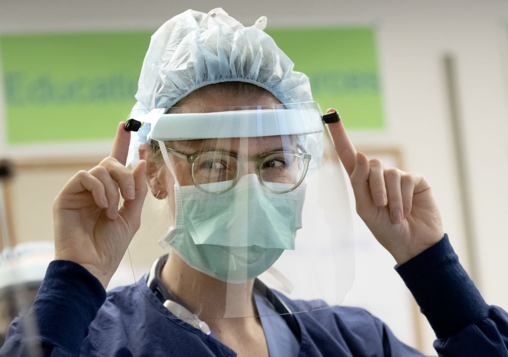 woman in medical scrubs wearing a full face shield