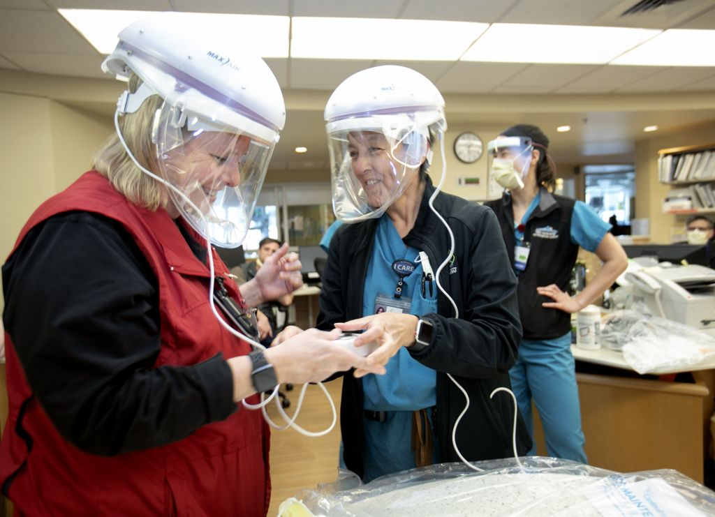 two women, both wearing white respirator helmets with plastic face shields, smiling and talking to one another