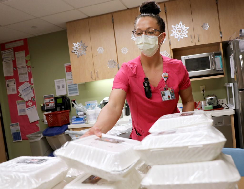 medical staff wearing pink scrubs and a face mask, distributing prepackaged meals