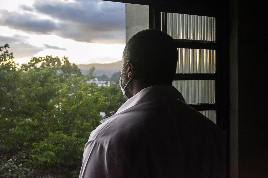 african american man with face mask looking out window
