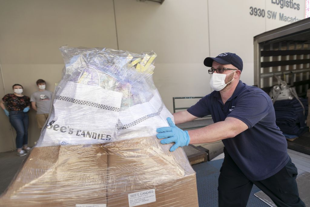 man wearing a medical mask, pushing a pallet full of See's candies up a ramp as he unloads a truck