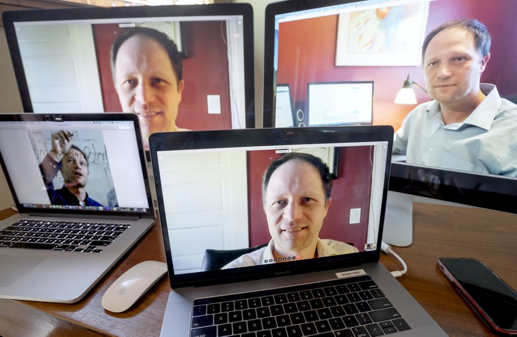 four computer monitors, all with peter graven's image in them. caucasian man, smiling