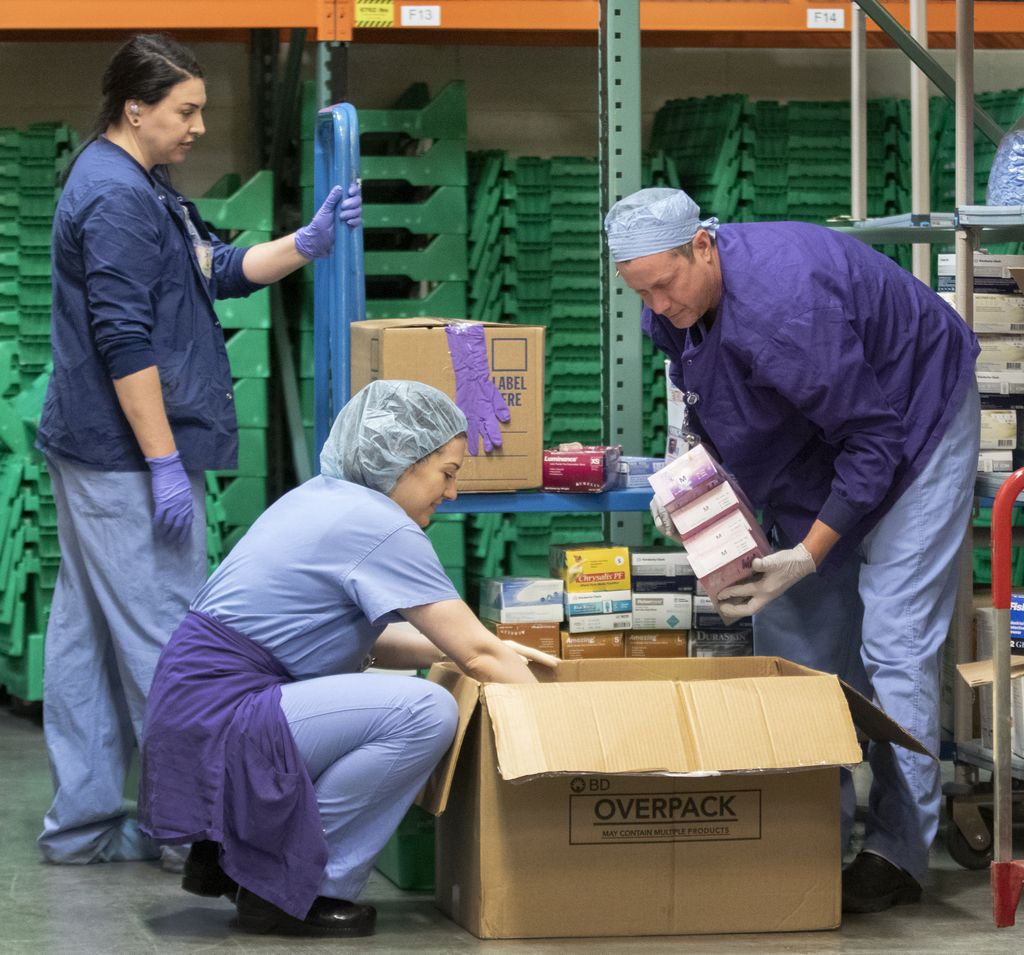 Health care workers in scrubs sorting donations