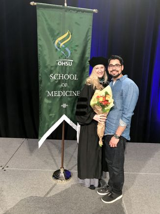 woman in green cap and gown, with her husband, in front of a sign for OHSU School of medicine graduation