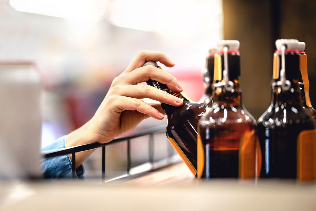 woman's hand reaching into shelf to take a bottle of beer