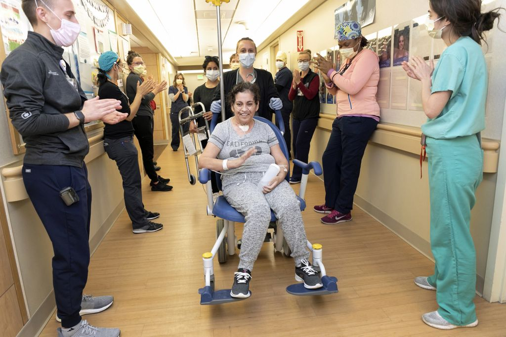 woman being wheeled out of a hospital down a hallway filled with people