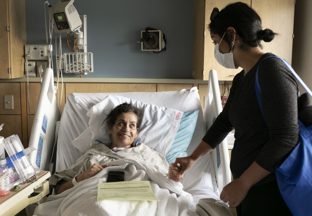 woman in her hospital bed holding her daughters hand and looking up to her
