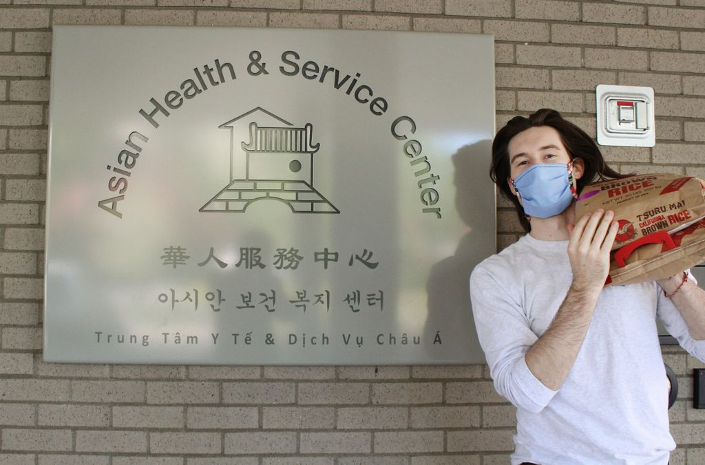 person holding a bag of rice on shoulder near a sign for the Asian health and service center