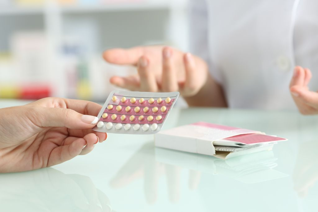 tight shot of person's hand, handing over birth control pills to a woman's hand