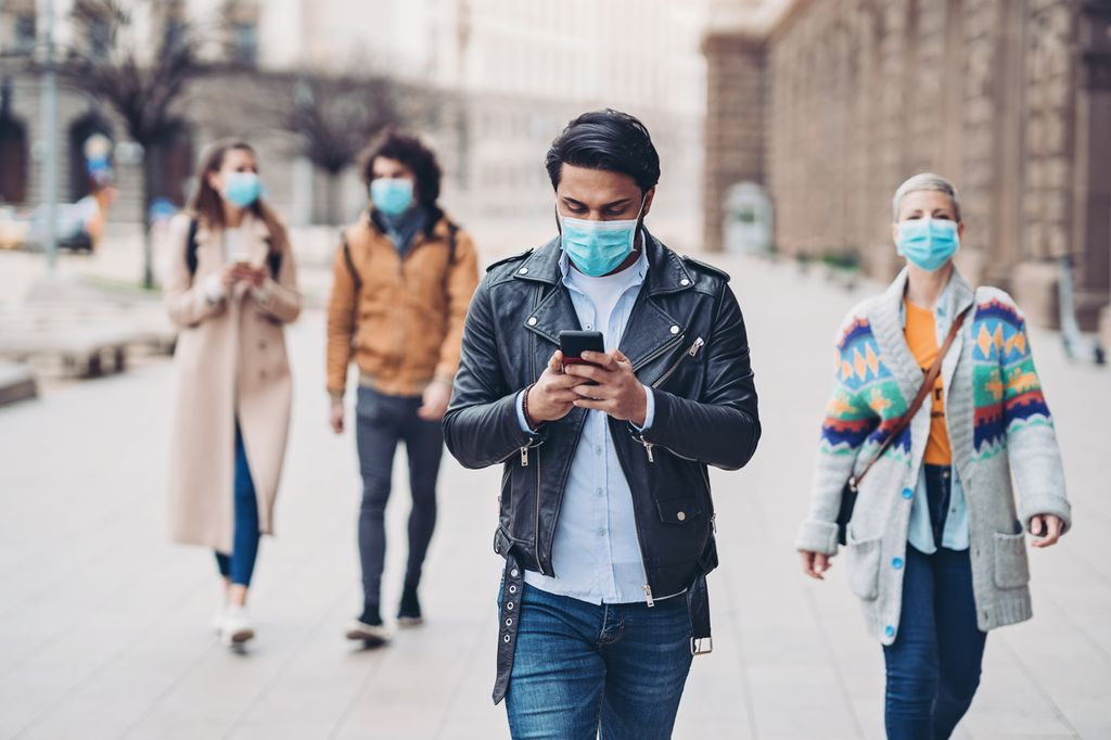 people walking in public, wearing protective masks