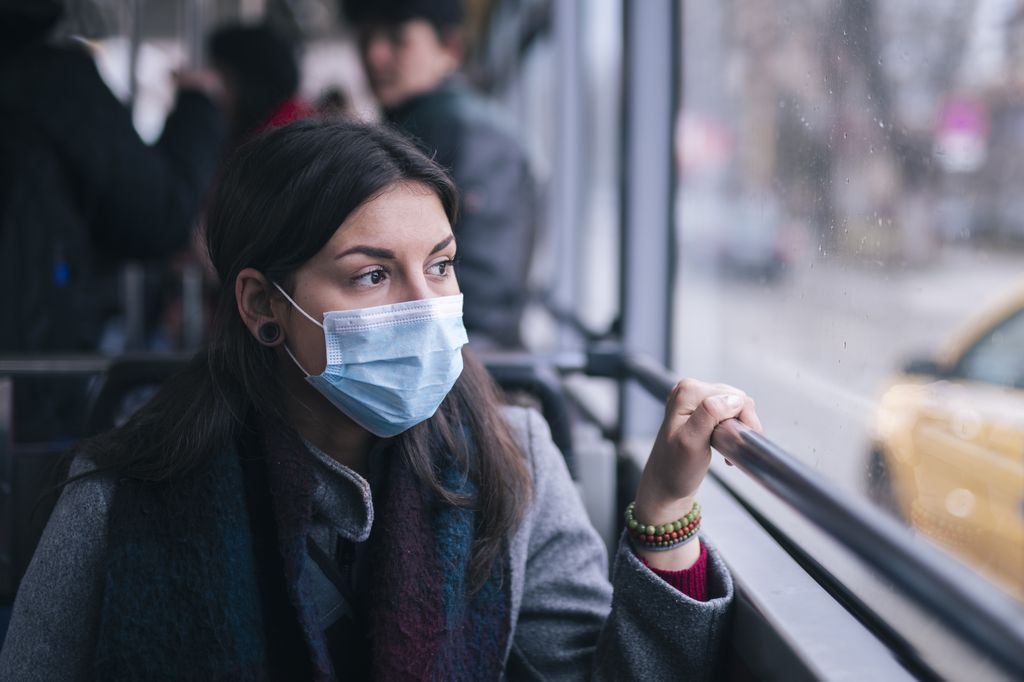 woman, wearing a mask, riding on a bus and looking out window, looking anxious