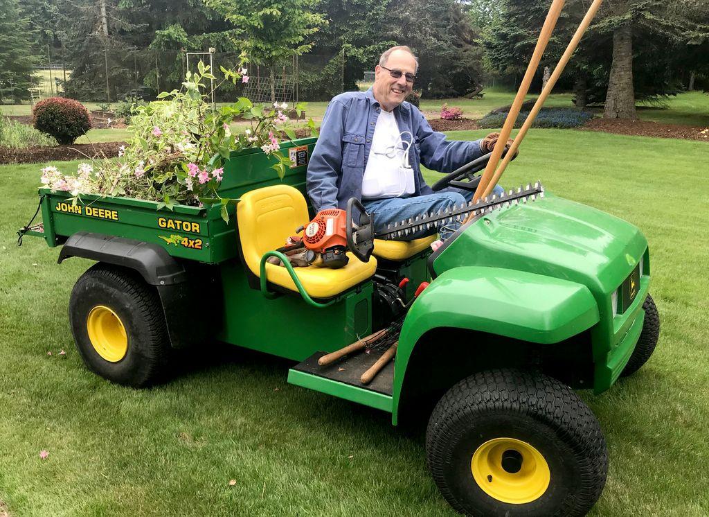 man on a fourwheel work gator, with chainsaw, working in garden