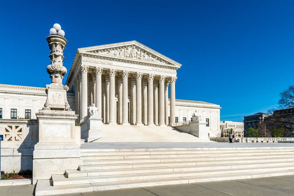 shot of the supreme court building and steps, with large pillars and statues outside