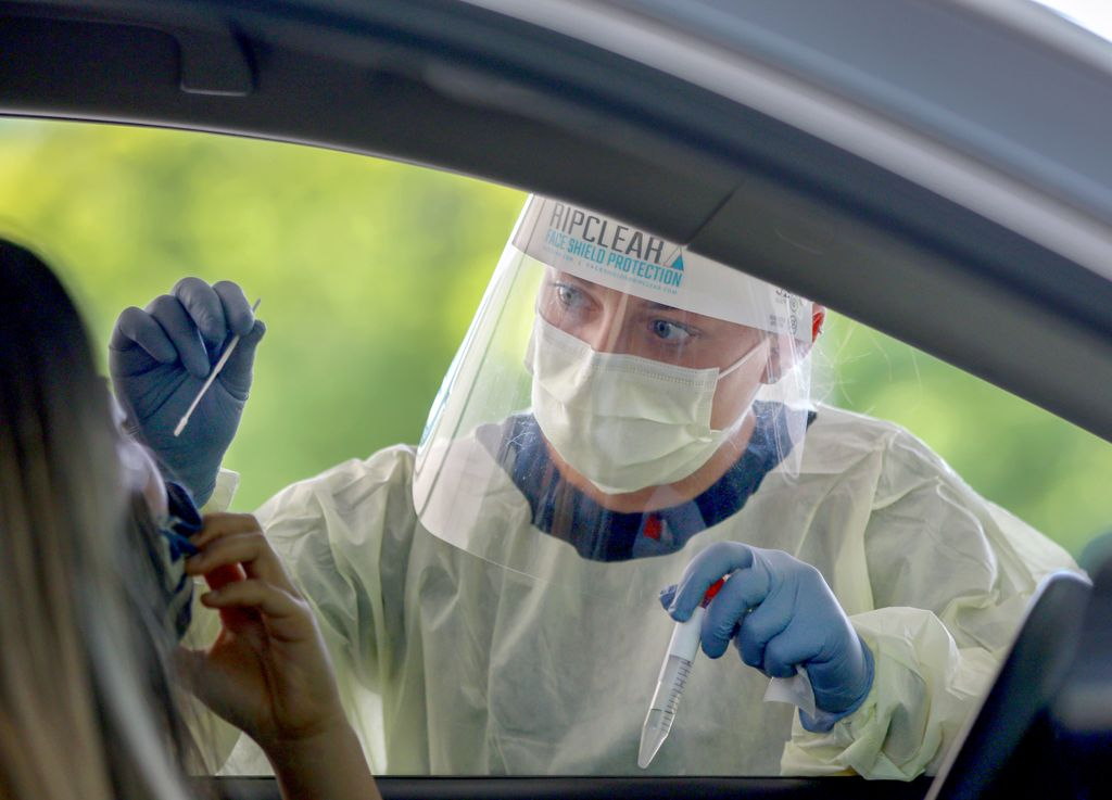 masked and gowned medical professional taking a nasal swab of a patient seated in a car