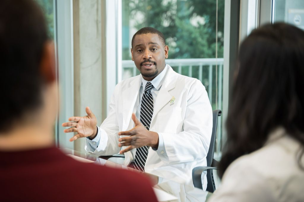 luke masha, seated at a table and talking with other docs, wearing a white coat