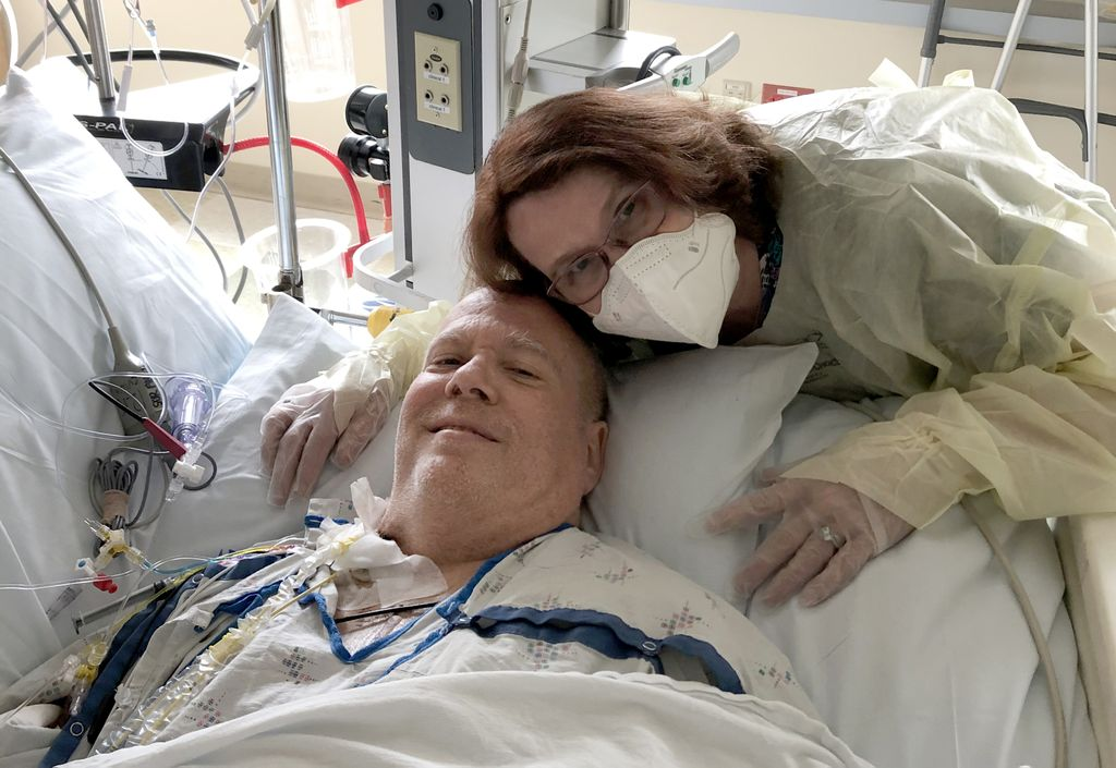 woman wearing a mask, hugging a man in a hospital bed, connected to a lot of machines and tubes