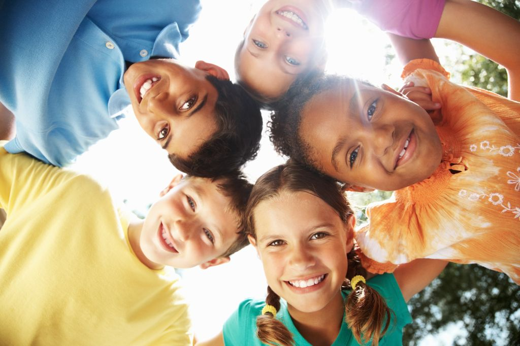 group of multiracial kids, standing in a circle looking down at camera, smiling