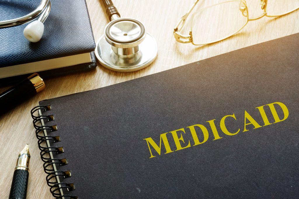 book with MEdicaid written across front, stethoscope and pencil lying nearby