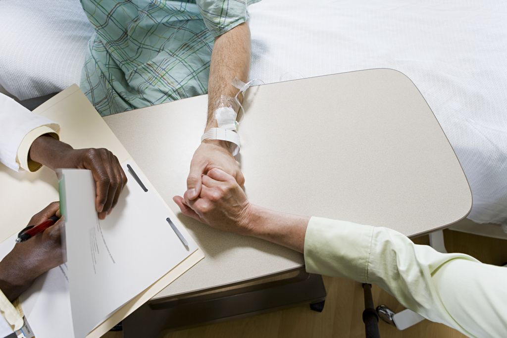 overhead image of someone in a hospital bed, holding hands with someone and talking to a doctor