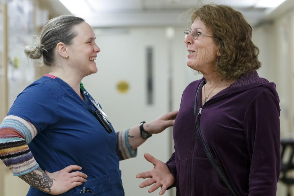 two woman laughing together in a hospital hallway
