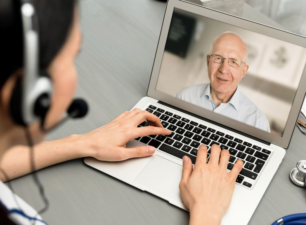 shot over the shoulder of someone wearing a headset, typing on the computer, talking to a senior on the computer