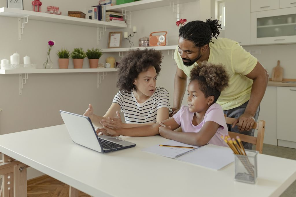 Black parents with their daughter, working on distance learning at a table with a laptop, pencils and notebook