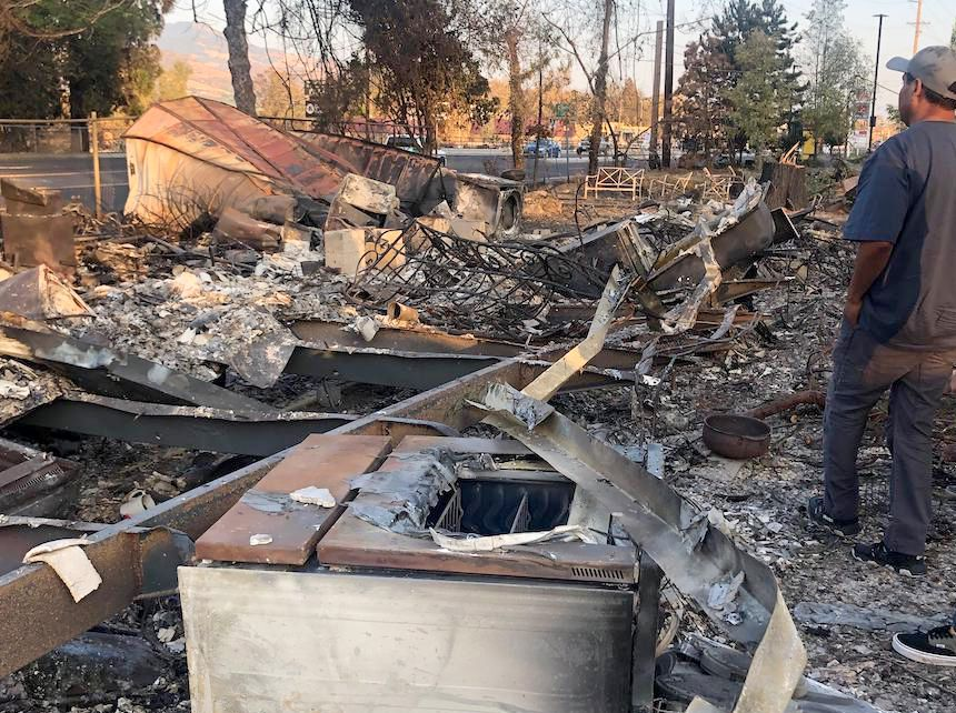 burnt out remains of a home following a wildfire, man standing to the right, seen from back, looking over remnants of the home