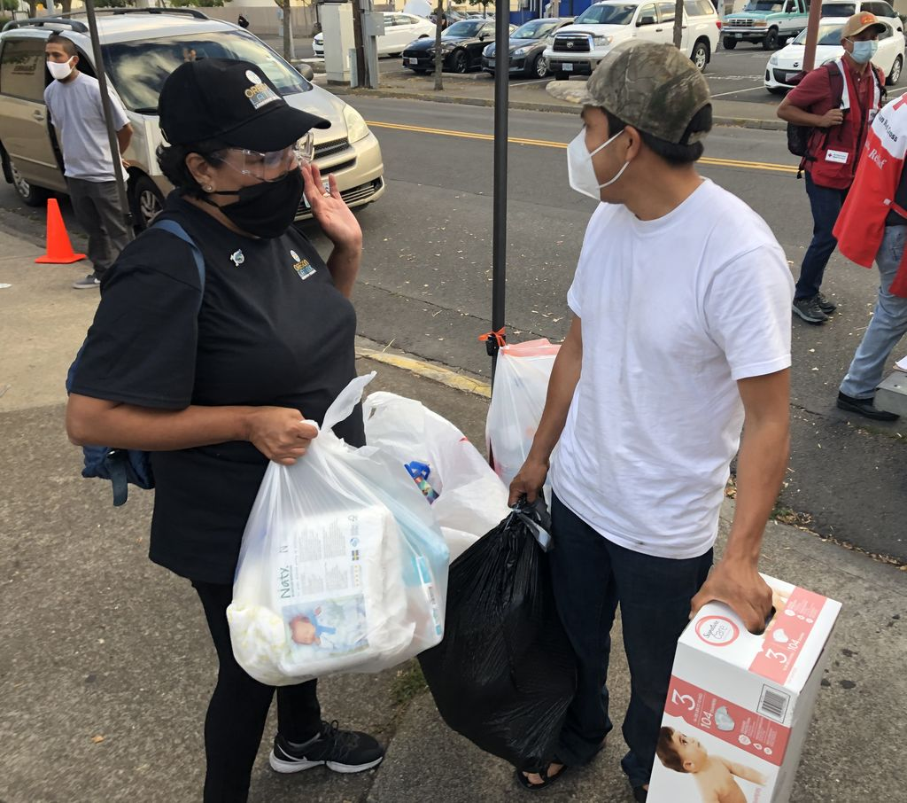 A masked female volunteer gives a box of diapers and bags of clothing to a masked man.